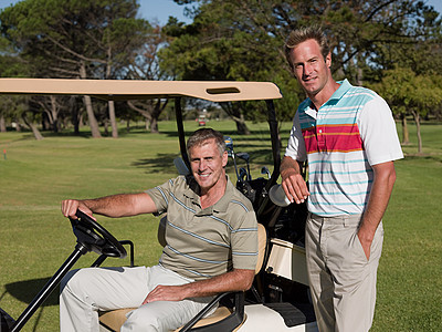 两个中年男子在高尔夫球场的高尔夫球车上图片