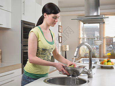 女人在厨房水槽里洗葡萄图片