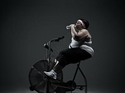骑健身车的超重妇女图片