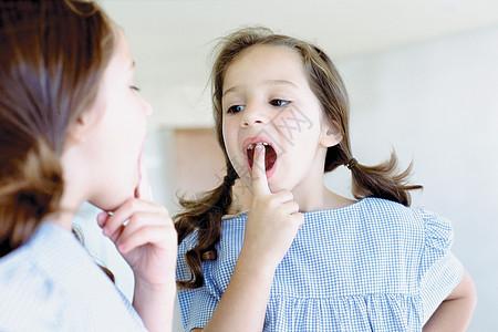 女孩看着镜子里丢失的牙齿图片
