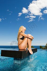 坐在游泳池平台上的女人图片