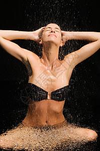 坐在淋浴下面的女人图片
