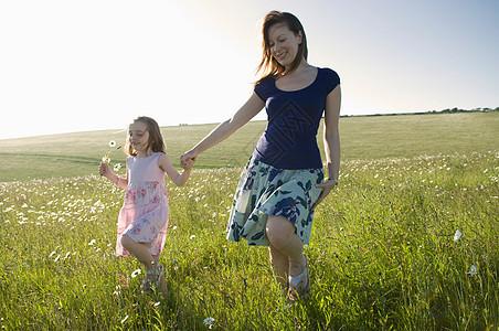 女人和孩子漫步在阳光明媚的草地上图片