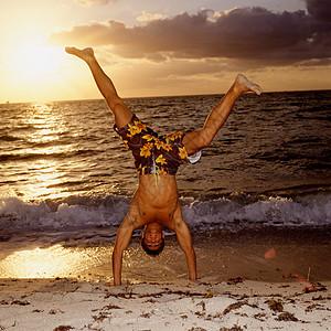 在海滩上做倒立的男人图片