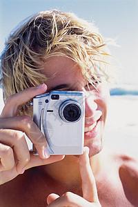 海滩上拍照的男人图片