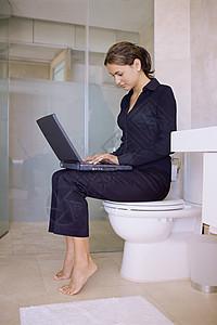 马桶上用笔记本电脑的女人图片