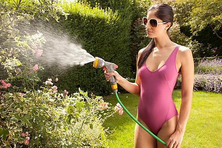 穿着泳衣的女人在浇花图片