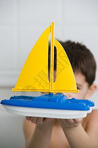 拿着玩具船的男孩图片
