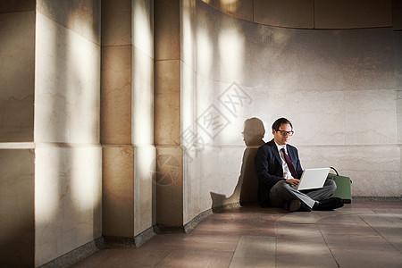 坐在地板上工作的人图片