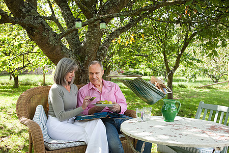 一对夫妇坐在户外椅子上吃下午茶图片
