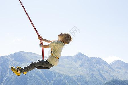 在奥地利蒂罗尔玩秋千的男孩图片