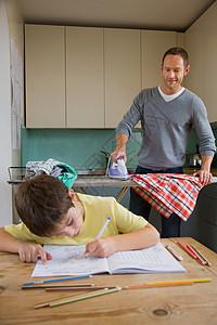 父亲在熨衣服和儿子在做作业图片