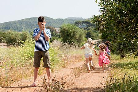 四个朋友在乡间小路上玩捉迷藏图片