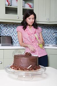 年轻女子吃芹菜看着巧克力蛋糕图片