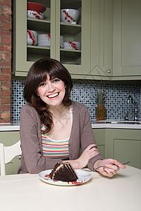 吃巧克力蛋糕的年轻女人图片
