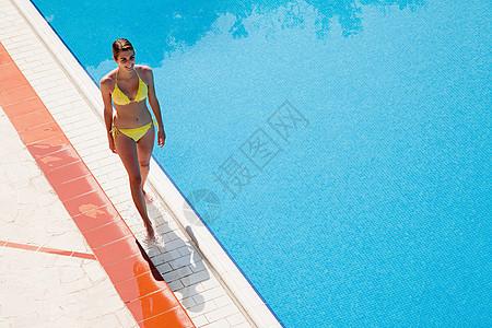 走在池边的年轻女子图片