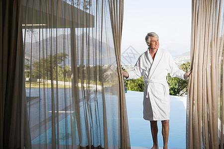 穿着长袍的中年男子拉开池边的窗帘图片