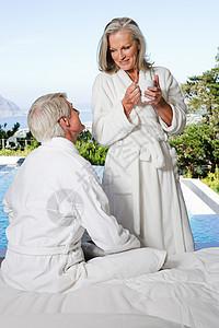 穿着浴衣的中年夫妇在泳池边图片