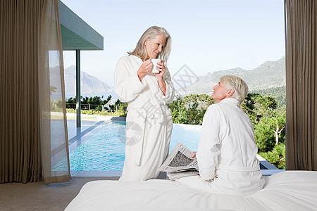 一对中年夫妇,卧室里有浴室,可以看到游泳池图片
