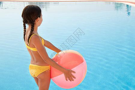 游泳池边有沙滩球的女孩图片