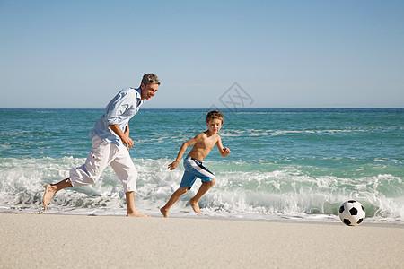 父子俩在海边踢足球图片