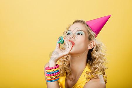戴着派对礼帽和派对彩带的年轻女子图片