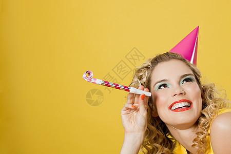 戴着派对帽带着派对吹风机的年轻女子图片