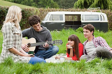 为野外朋友弹吉他的年轻人图片
