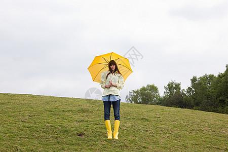 带伞的田里年轻女子图片