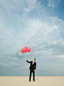 商人拿着一堆红气球图片