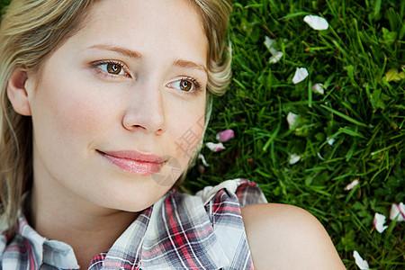 躺在草地上的年轻女子的脸图片