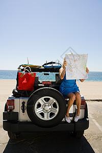 坐在车上看地图的年轻女子图片