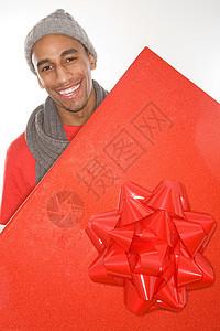 拿着一个大红色礼物的男人图片