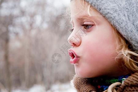 小女孩在寒冷的空气中看着她的呼吸图片