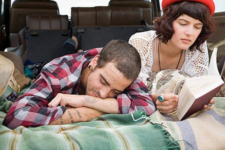 一对躺在SUV后面的夫妇图片