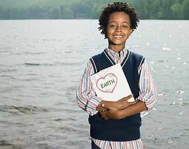 一个男孩在湖边拿着一本书图片