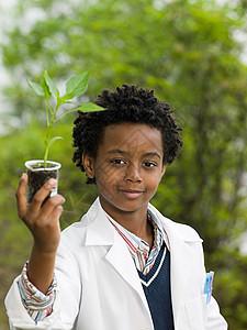 把植物放在容量瓶中的男孩图片
