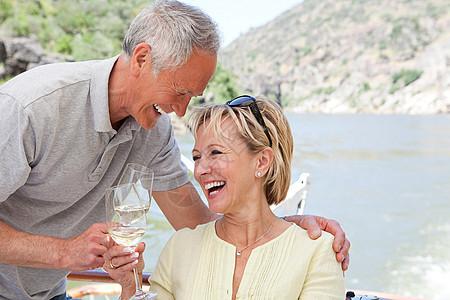 在船上度假时带着酒杯的老年夫妇图片