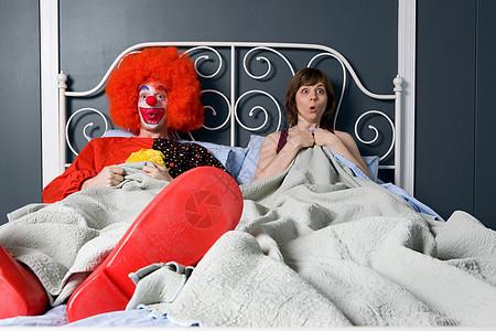 小丑和女人惊奇地发现他们在床上在一起图片