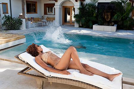 在游泳池边躺着晒太阳的女人图片