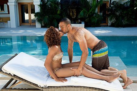 一对情侣在游泳池边的日光浴椅上接吻图片