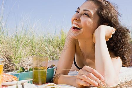 在野餐毯上笑的女人图片