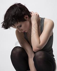 摄影棚拍摄的性感年轻女子蹲下俯视图片