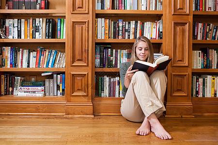 坐在书架上看书的年轻女子图片