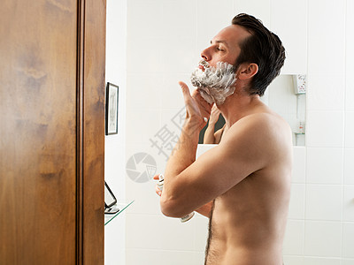 在浴室用剃须泡沫的男士图片