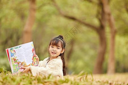 小女孩户外看童话书图片