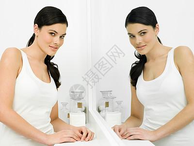 浴室镜子中年轻女子图片