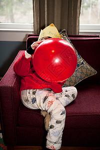 吹起红色生日气球的男孩图片