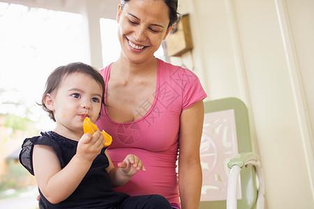 妈妈看着吃橘子片的女儿图片