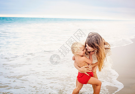 妈妈抱着女儿在海滩上图片